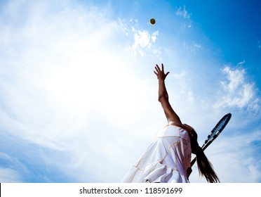 Tennis woman in a white tennis dress developing ball service