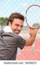tennisplayer all smiles holding racket near court