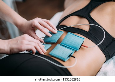 TENS, Transcutaneous Electrical Nerve Stimulation in Physical Therapy. Therapist Positioning Electrodes onto Patient's Lower Back