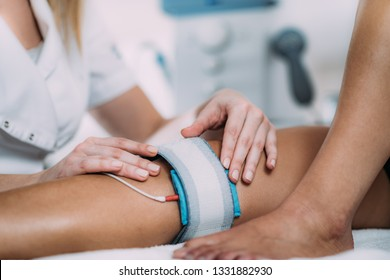 TENS, Transcutaneous Electrical Nerve Stimulation in Physical Therapy. Therapist Positioning Electrodes onto Patient's Knee