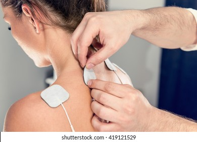 TENS treatment in physical therapy - therapist placing electrodes onto patient