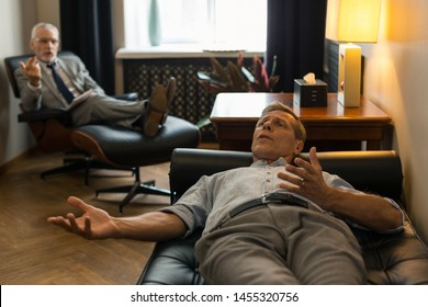 Tense man. Tense Caucasian male patient lying on the couch in front of his psychotherapist while complaining about his problems