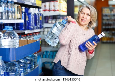 Tense modern woman lifting heavy bottle of still water while shopping at grocery store