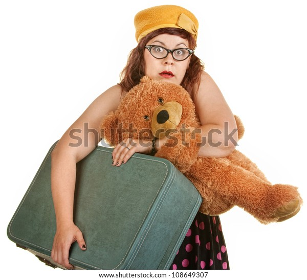 Tense young woman with toy bear and suitcase