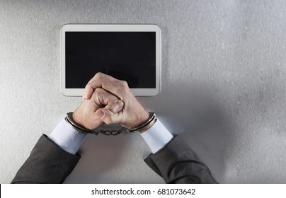 tensed businessman fists facing a digital tablet with handcuffs for concept of modern technology slavery, hostage or victim of corporate communications dependency, top view