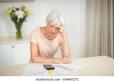 Tensed senior woman sitting in kitchen at home