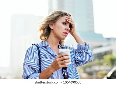 Tensed woman with the coffee take away cup