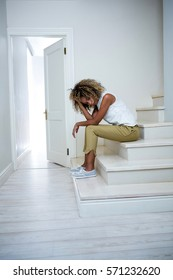 Tensed woman sitting on stairs at home