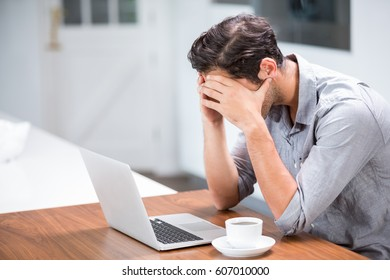 Tensed young man with head in hands while sitting at laptop desk