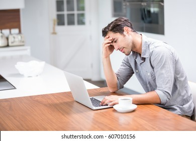 Tensed young man using laptop at home