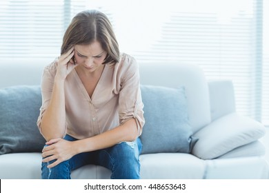 Tensed young woman sitting on sofa at home