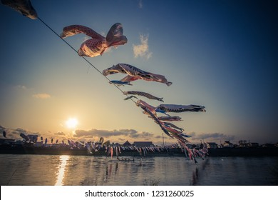 Tenshochi Park,Kitakami,Iwate,Tohoku,Japan on April 26,2018:Carp streamers (or koinobori) over the Kitakami River blowing in strong wind during sunset