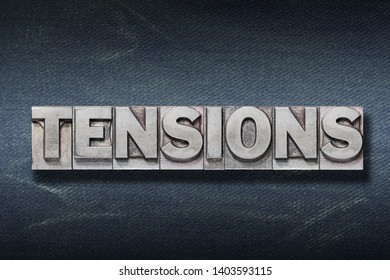 tensions word made from metallic letterpress on dark jeans background