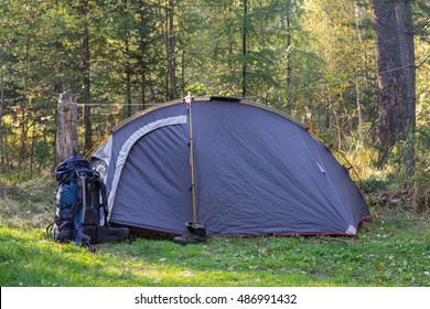 A tent and a backpack with boots in the forest at sunny sunset