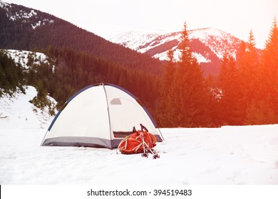 Tent with backpack in winter mountains. Concept of success living and free traveling, active leisure, health care and well being.