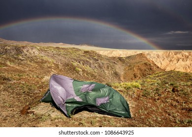 Tent broken by strong wind and a rainbow in Zhabyr Canyon (Yellow canyon) in National park Charyn,  Kazakhstan