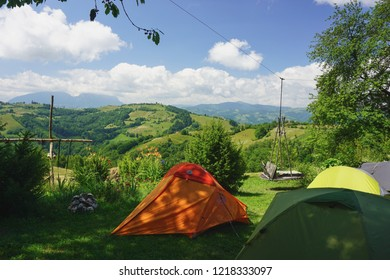 Tent camp in rural countryside campground in Transylvania, Romania, on a sunny day of summer with green grass hills. ecotourism