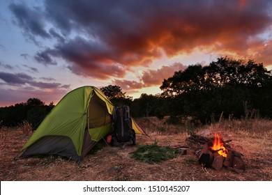 Zelt und Lagerfeuer in Malabotta Natural Reserve bei Sonnenuntergang, Sizilien