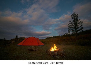 A tent and campfire under an evening sky full of red clouds