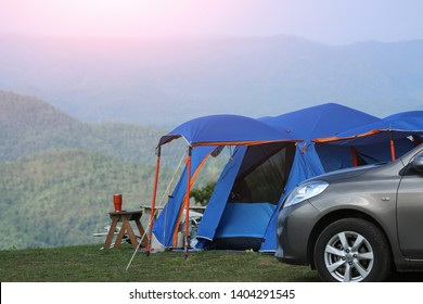Tent Camping in the Forest. Traveling by Car and Camping with a Tent. Morning landscape with  tent and car, the mountain in the background. Summer camping.