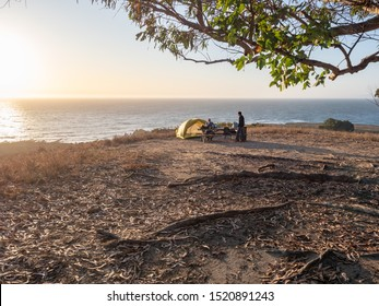 Tent campsite with family on bluff over ocean at sunset in Montana de Oro State Park, Los Osos, California, USA