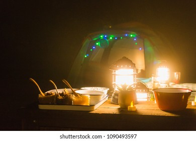 Tent and campsite at night lit by lanterns and colored led lights in a forest