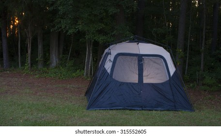 Tent with a dim light inside as the sun is setting through the forest
