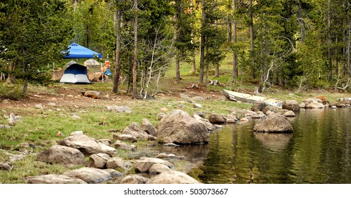 A tent and eating area set up in a rugged campsite in the mountains, with a rowboat at the edge of a lake.
