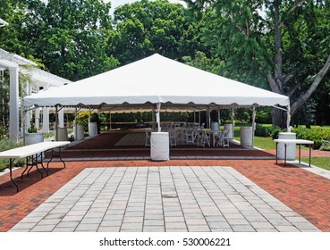 Tent event tent. Empty. Nobody. Horizontal. Brick and stone patio in foreground. Horizontal.