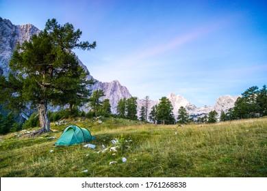 A tent glows under a moon night sky at twilight hour. Julian Alps, Triglav National Park, Slovenia. View from Mount Slemenova, Sleme to Mountain Jalovec.