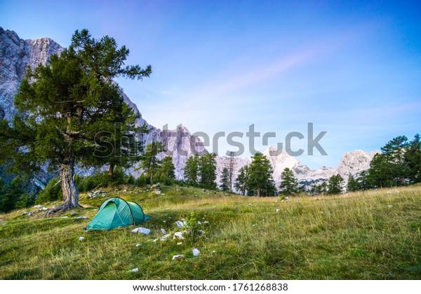 Une tente brille sous un ciel étoilé à l'heure du crépuscule. Alpes Juliennes, Parc national de Triglav, Slovénie. Vue du mont Slemenova, de Sleme à Mountain Jalovec.