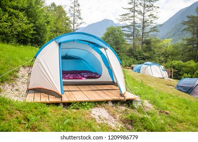 Tent interior with mattresses and purple duvet covers on wooden platform.