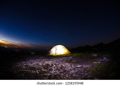 A tent lit from the inside with light painting on the ground around it