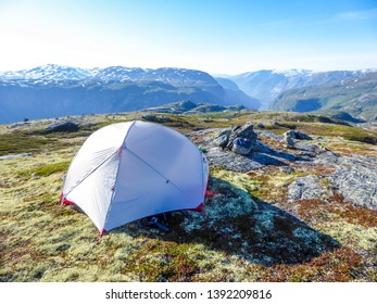 A tent located on a meadow, high in the mountains with the view on Eidfjord, Norway. Camping in the wilderness. Adventurous travels, living life to the fullest. Freedom and relax