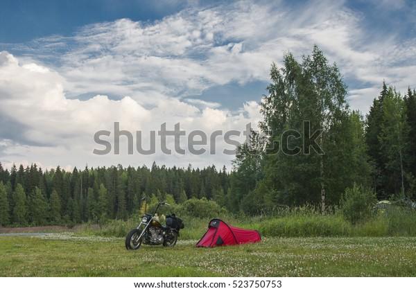 Tent with motorbike next to scandinavian lake at summer