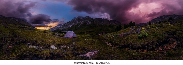 tent in the mountains against the backdrop of purple clouds at sunset. Cylindrical 360 panorama