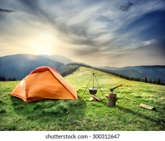 Tent on the hill beneath the mountains under dramatic sky