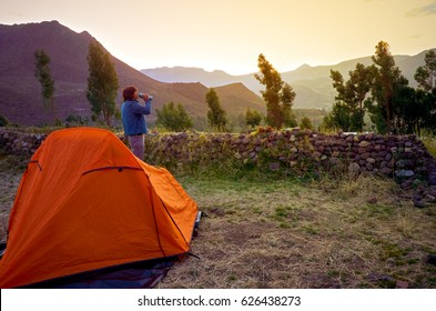 Tent with person drinking water at sunrise