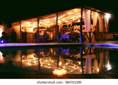 Tent restaurant at night on the background of a large swimming pool. People celebrate the wedding at a restaurant outdoors.