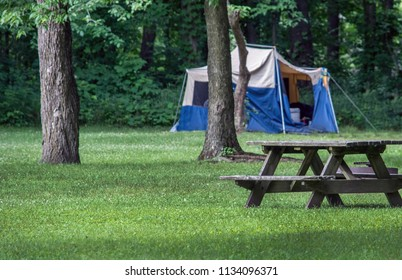 A tent is set up in an Indiana park, near a picnic table and a grove of trees
