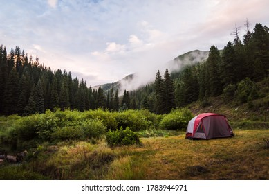 A tent set up in the mountains during sunset.