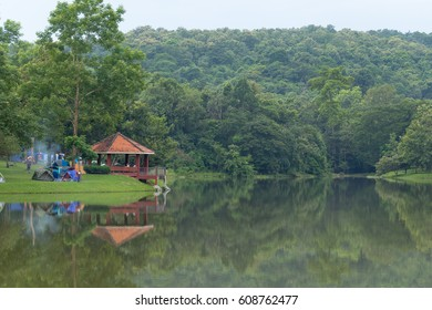 tent is spread by the reservoir near the mountain with the forest covered.