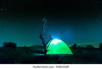 A tent in the woods under a star filled sky.