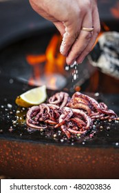The tentacles of the squid on the grill in the background fire Hand rolling in salt. Selective focus