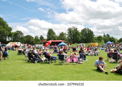 TENTERDEN, ENGLAND - JUNE 30: The audience sitting on the grass at the Tentertainment music festival on June 30, 2012 at Tenterden, Kent. The annual free event was first held in 2008.