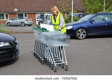 TENTERDEN, ENGLAND - MAY 17, 2012: A female employee collects shopping trolleys outside a branch of supermarket chain Waitrose in Kent, England. The first Waitrose supermarket opened in 1955.
