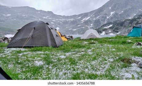 Tents during hail and cold rain in Summer, midday at Lake Bucura, Retezat mountains. View from inside a tent, with lots of hailstones in the green grass. Severe weather conditions in the mountains.