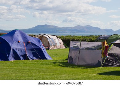 Tents on campsite with a view of the Menai Strait and snowdonia mountains in Wales UK.