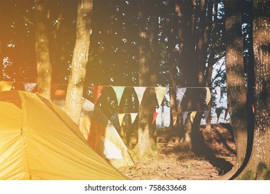 Tents pitched at a campsite amongst trees with garlands of colorful festive bunting or flags strung between trunks with the sun glow in the left corner