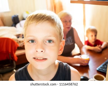 A ten-year-old Caucasian boy posing against the backdrop of his grandmother and younger brother sitting by the computer